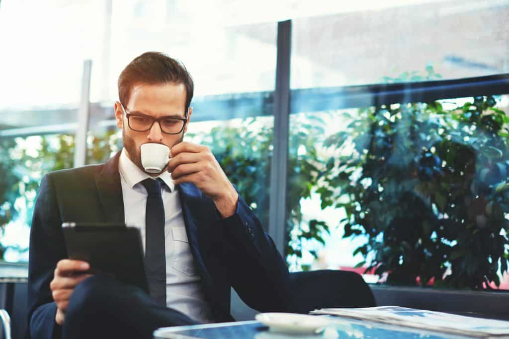 Male small business owner drinking espresso and reading a business book on ipad