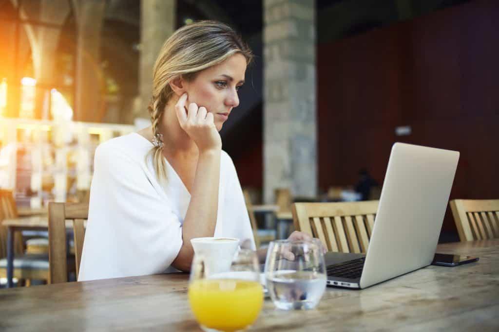 Female entrepreneur taking online classes at a cafe