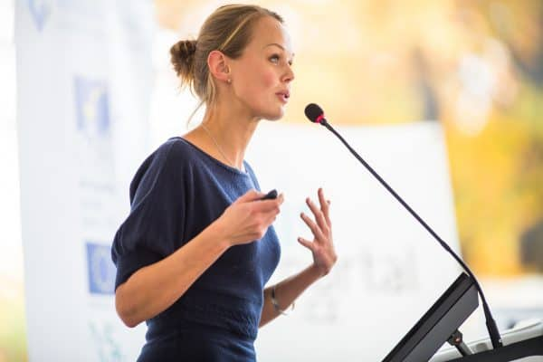 Female business owner gives a business presentation on a microphone