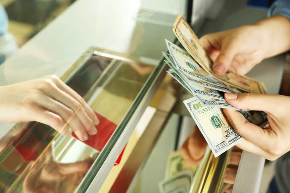 small business owner getting cash from a bank teller