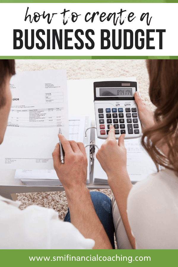 Man and woman using a calculator and stack of bills to create a business budget