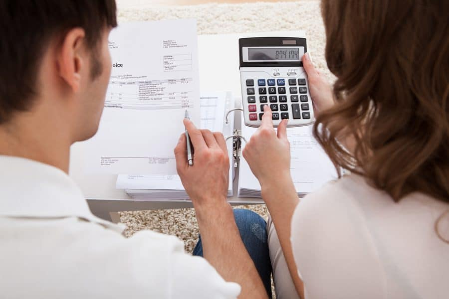 Two business owners learning how to create a business budget with a calculator and business budget template.