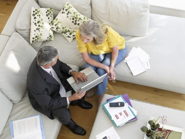 Business coach sitting in living room with woman discussing finances.