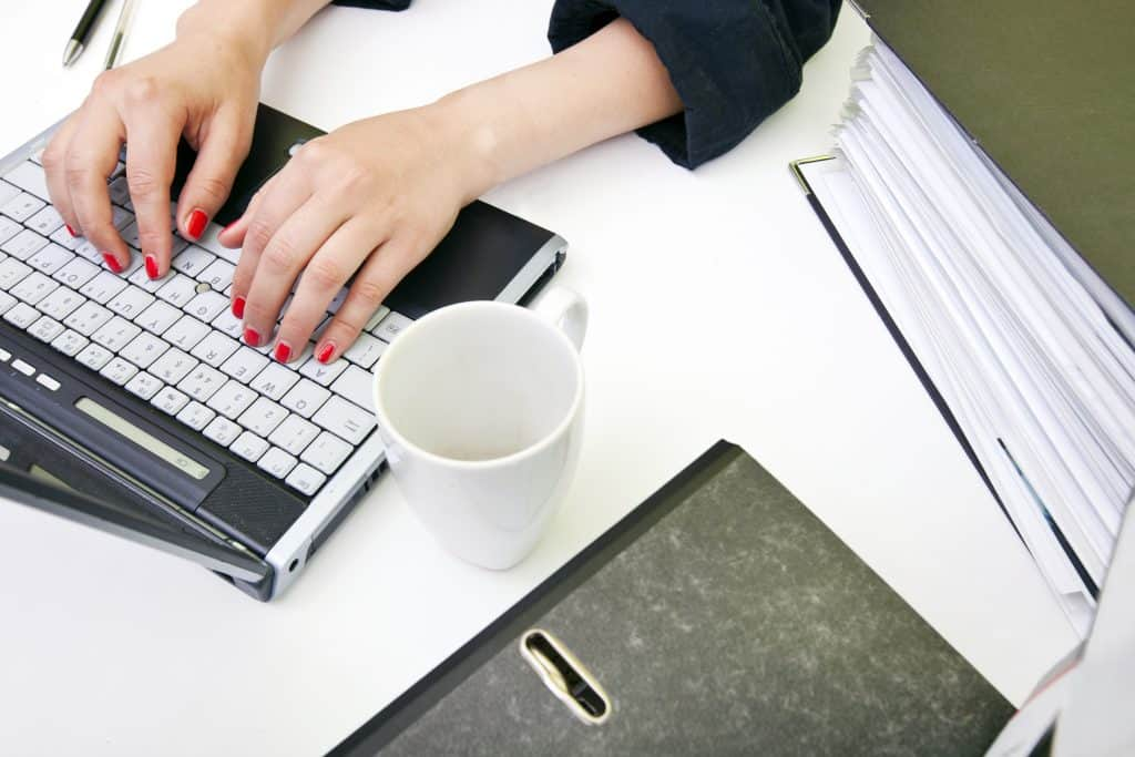 Woman writing a business plan on a laptop with red nail polish on, and a coffee cup.