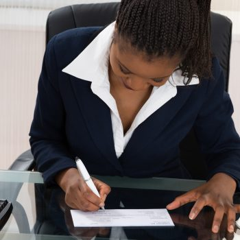 business owner signing her own paycheck