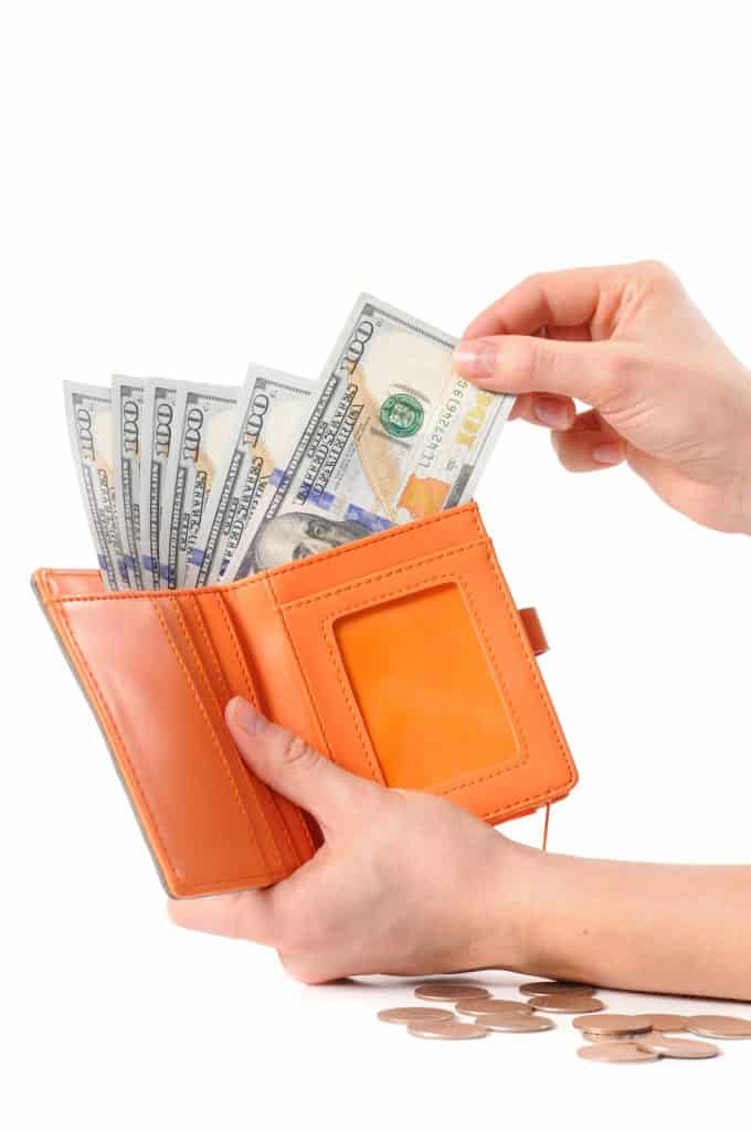business owner holding a wallet full of cash