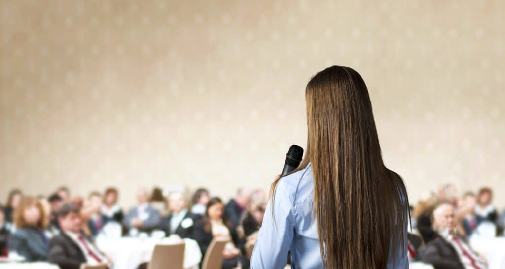 woman speaking at a conference to an audience