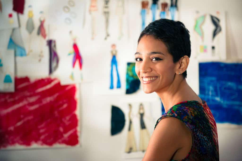 Fashion designer studying designs to determine worth